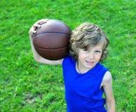 拿着球的年轻蓝球运动员 免版税图库摄影