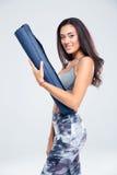 拿着瑜伽席子的一名愉快的健身妇女的画象 免版税库存照片
