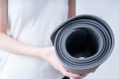 拿着瑜伽席子 免版税图库摄影
