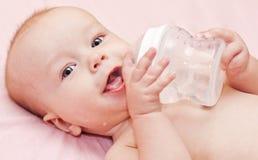 拿着瓶和饮用水的愉快的婴孩 图库摄影