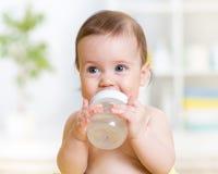 拿着瓶和饮用水的甜婴孩 库存图片