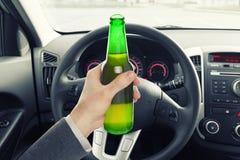 拿着瓶啤酒的人,当驾驶时 免版税库存照片