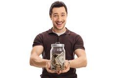 拿着瓶子的快乐的人有很多金钱 免版税库存照片