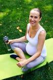 拿着瓶水的莲花姿势的怀孕的女性 免版税库存图片
