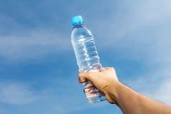 拿着瓶淡水的一只人的手 免版税库存照片