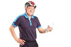 拿着瓶的成熟骑自行车者 图库摄影
