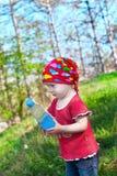 拿着瓶的明亮的衣裳的小美丽的女孩手中 免版税图库摄影