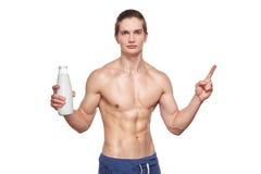 拿着瓶的英俊的年轻肌肉运动员 免版税库存图片