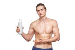 拿着瓶的英俊的年轻肌肉运动员 免版税库存照片