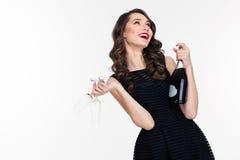 拿着瓶香槟和两块玻璃的可爱的无忧无虑的妇女 库存照片