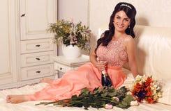 拿着瓶香槟的美丽的微笑的新娘 免版税图库摄影