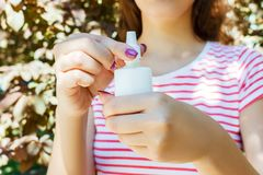 拿着瓶鼻孔喷射的女性手在公园 库存照片