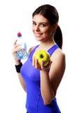 拿着瓶水和苹果的年轻微笑的体育妇女 免版税库存图片