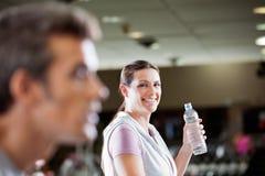 拿着瓶水的妇女在健身俱乐部 免版税库存照片
