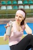 拿着瓶水的年轻休息的女运动员 图库摄影