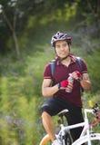 拿着瓶水的年轻男性骑自行车者 免版税库存图片