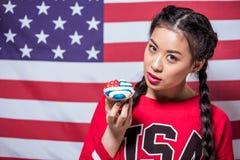 拿着甜点装饰美国国旗和看照相机的妇女画象 库存照片