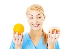 拿着甜食物和桔子在白色背景的护士 免版税图库摄影