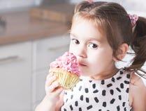 拿着生日杯形蛋糕的逗人喜爱的小女孩在厨房里 欢乐和假日概念 图库摄影