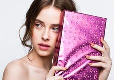 拿着生日礼物箱子礼物的愉快的逗人喜爱的女孩 免版税库存照片