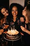 拿着生日蛋糕的年轻愉快的妇女 免版税图库摄影