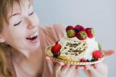 拿着生日蛋糕的愉快的可爱的少妇 库存图片