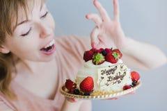 拿着生日蛋糕的愉快的可爱的少妇 免版税库存图片