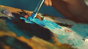 拿着用不同的油漆的女性艺术家的手肮脏的调色板 股票视频