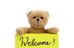"""拿着用两只手在明亮的黄色颜色的玩具熊笔记与手写的消息""""Welcome! 作为可喜的迹象的† 免版税库存图片"""