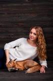 拿着由一个人受损伤并且在她和现在生活之前抢救作为以前的一个野生狐狸动物的一个年轻美丽的女孩 免版税库存照片