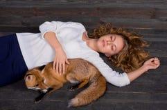 拿着由一个人受损伤并且在她和现在生活之前抢救作为以前的一个野生狐狸动物的一个年轻美丽的女孩 库存照片