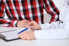 拿着申请表的一位女性医生的特写镜头,当咨询患者时 免版税图库摄影