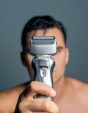 拿着电动剃须刀的手 免版税图库摄影