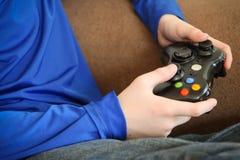 拿着电子游戏控制器的男孩 免版税库存照片