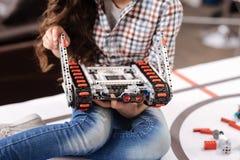 拿着电子玩具的小女孩在机器人学实验室 免版税图库摄影