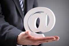 拿着电子邮件的商人在标志 免版税库存照片