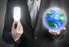 拿着电灯泡和行星地球的生意人 免版税库存照片