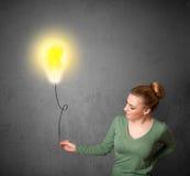拿着电灯泡气球的妇女 免版税图库摄影