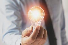 拿着电灯泡的商人手 与innovatio的想法概念 免版税库存照片