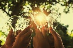 拿着电灯泡的太阳能概念手小组 库存图片