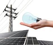 拿着电灯泡的手 在背景太阳电池板和高压塔 图库摄影