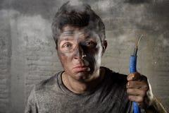 拿着电缆的年轻人抽烟在与肮脏的被烧的面孔的电子事故以后在滑稽的哀伤的表示 免版税库存照片