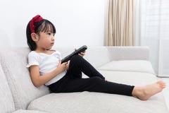 拿着电视的亚裔中国小女孩遥控 库存照片