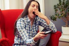 拿着电视的打呵欠的妇女遥控 免版税图库摄影