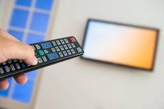 拿着电视遥控与电视作为背景 免版税库存照片