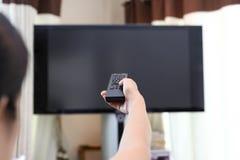 拿着电视遥控改变的电视频道的手 图库摄影