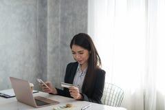 拿着电话和信用汽车的美丽的亚裔年轻女实业家 免版税库存图片