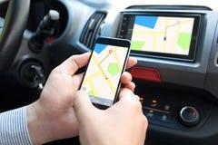 拿着电话和多媒体系统与地图的汽车的人 库存图片