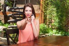 拿着电话和指向照相机的妇女室外 库存图片