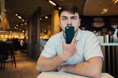拿着电话在面孔一个年轻人的画象和困惑的看看照相机 库存照片